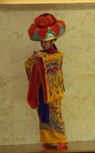 Yotsudake Classical dance. The big red had is called a Hanagasa, which means flower hat. Blue waves and bingata colors represent the Okinawan female spirit.